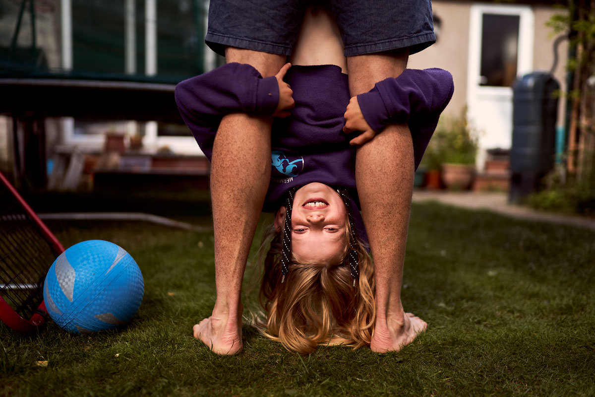 dad hanging daughter upside down by her feet