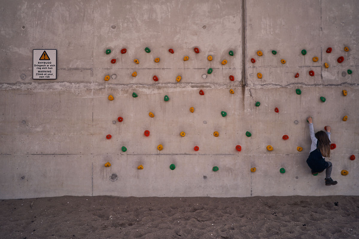 young child climing a climbing wall on the beach