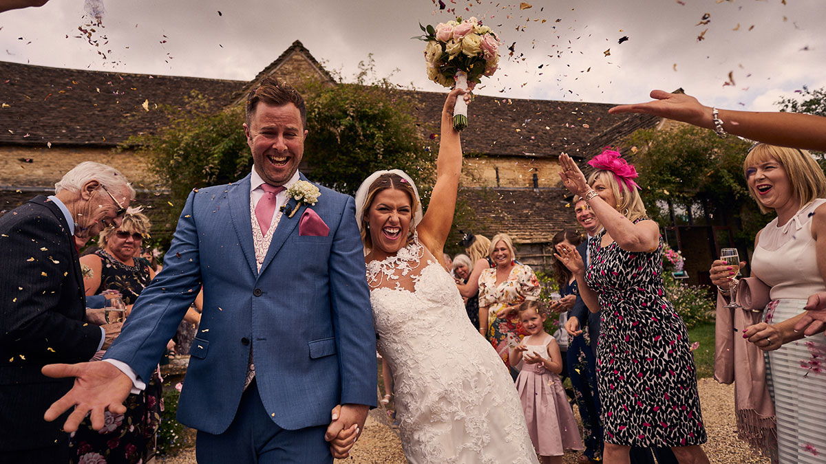 Bride & groom having confetti thrown at them when leaving The Great Tythe Barn