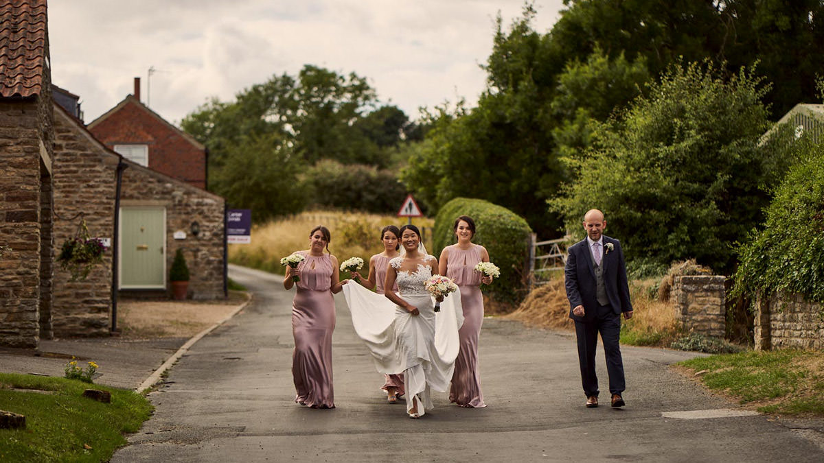 Bridal party walking to the church in Terrington, yorkshire