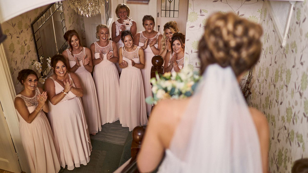Bridesmaids reaction to seeing bride walking down the stairs. Llandudno Wedding Photographer