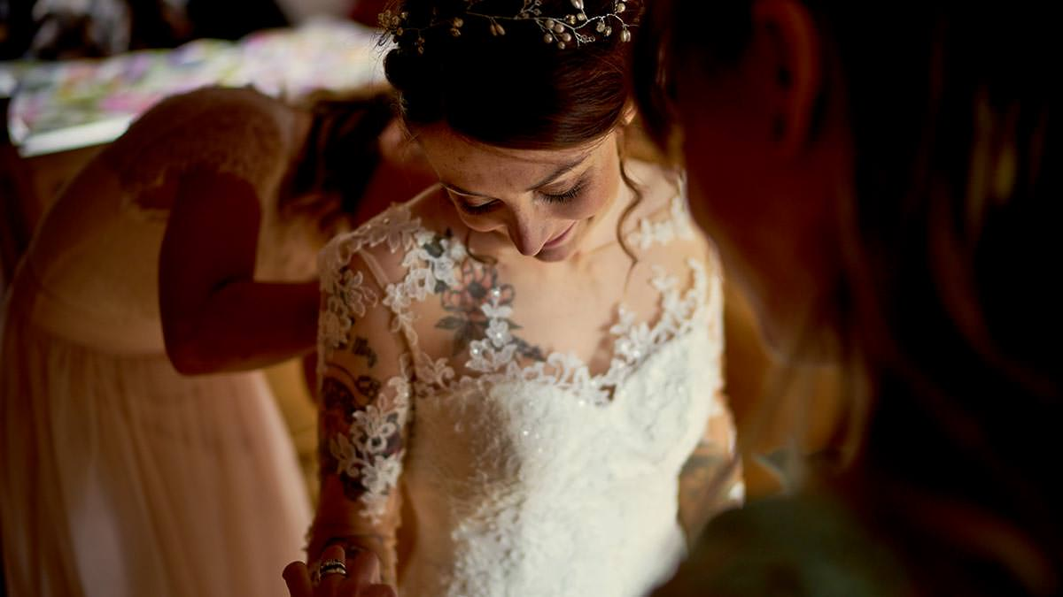 Tattooed bride getting her dress on
