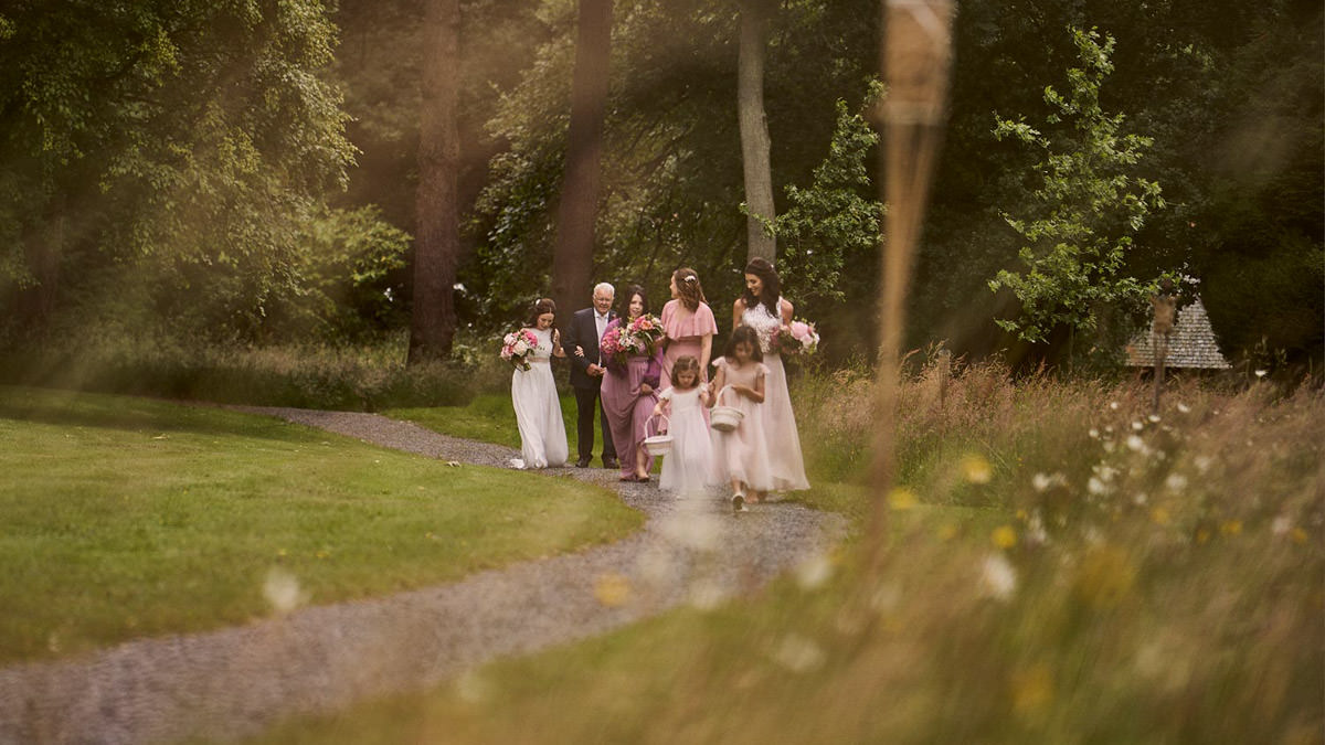 Bride walking with bridesmaids to her outdoor wedding ceremony at Plas Dinam, Mid Wales