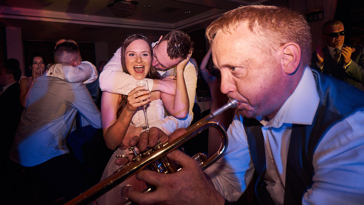 groom kissing and hugging bride on the dancefloor while The Brass Monkees play trumpet around them