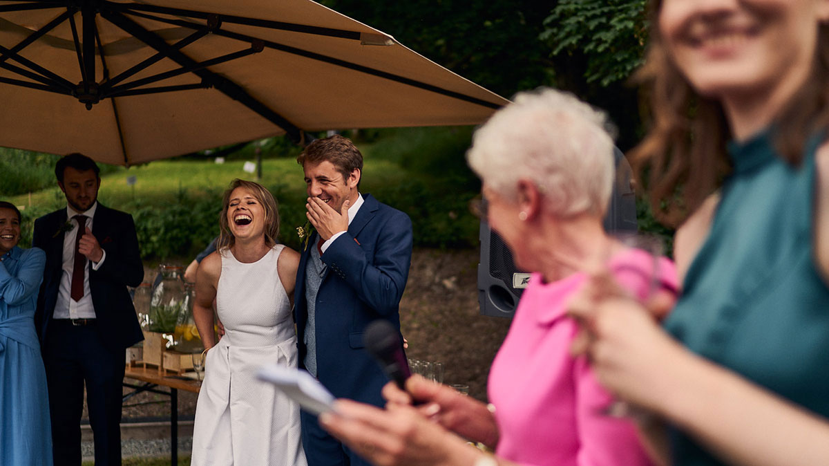 bride and groom laughing during outdoor speeches