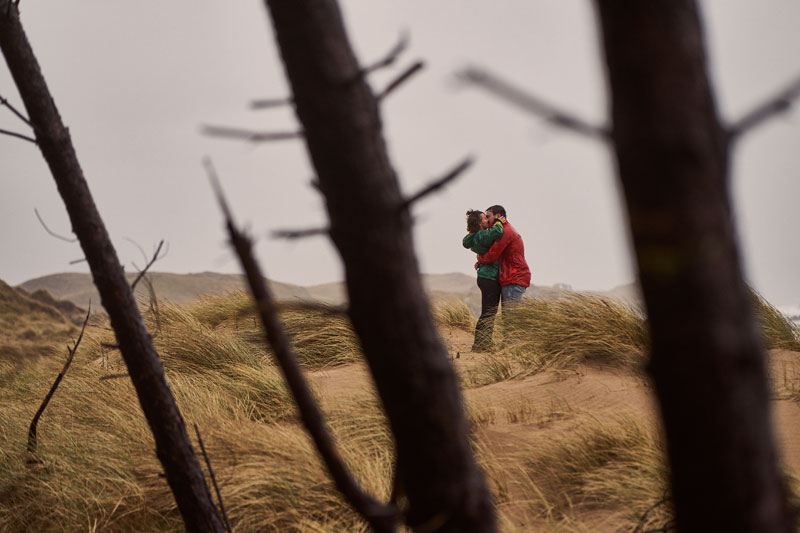 couple kissing in sand dunes after getting engaged